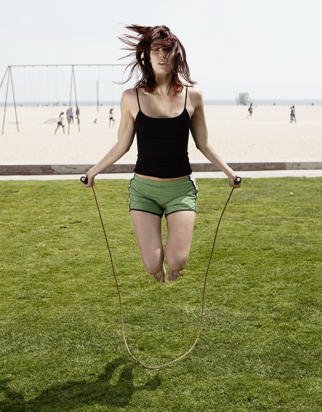 young attractive girl jumps with a skipping rope