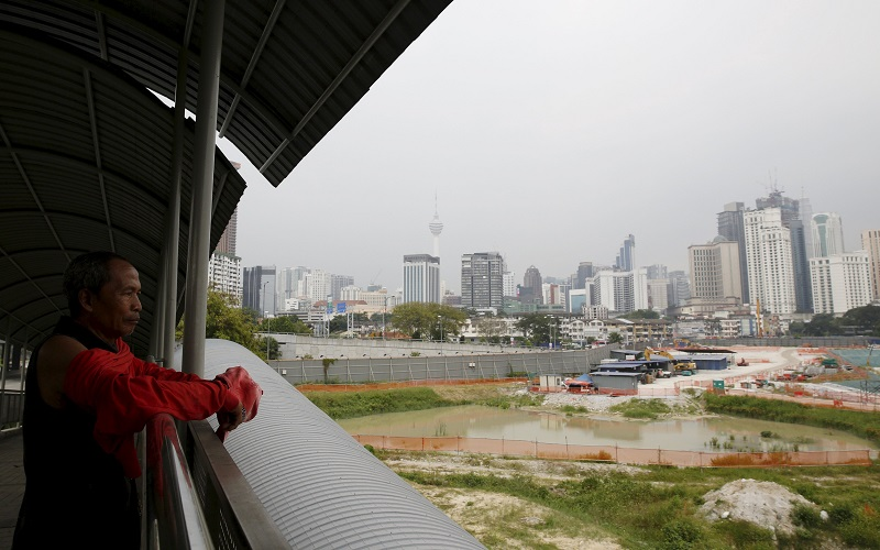 "A man looks out at 1 Malaysia Development Berhad (1MDB) flagship Tun Razak Exchange development in Kuala Lumpur, Malaysia, July 3, 2015. Malaysian Prime Minister Najib Razak slammed a report that said close to $700 million was wired to his personal account from banks, government agencies and companies linked to the debt-laden state fund 1MDB, claiming this was a ""continuation of political sabotage.""  REUTERS/Olivia Harris"