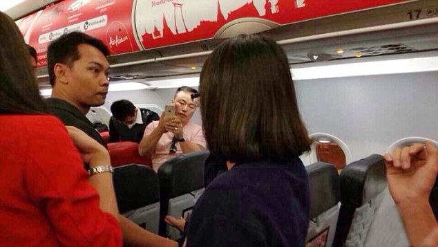 """Pic shows: A Chinese couple got into a furious row with cabin crew on a flight. A Chinese couple who got into a furious row with cabin crew on a flight could find themselves separated for quite some time after the incident escalated when hot noodles were thrown into the face of a hostess. The incident which happened on a Thai AirAsia plane was captured on video camera and on mobile phone snaps taken by other passengers that show one of the hostesses touching her face after being scalded when she was hit with a hot dish. She was reportedly given first aid on board by her colleagues to deal with the burns and was taken to hospital after the flight turned around and landed back in the Thai capital Bangkok. The trouble started when the couple boarded the plane and found themselves seated separately on the charter flight from Bangkok to the Chinese city of Nanjing. And even though the seating was rearranged to put the couple together, they were still angry and refused to calm down. The video clip showing the man shouting at staff who are trying to restrain him quickly went viral after it was uploaded on Chinese social media network Weibo. A spokesman for the budget airline said that the plane had been forced to turn round so that the angry couple could be arrested. The spokesman said that the decision to turn around had been made after the man claimed to have a bomb and threatened to blow the plane up. Photos later showed the man being led off the plane while carrying a young girl although he and the child and his girlfriend were not immediately arrested. He claimed that the hostess had been scalded by accident when they had argued with her over the receipt they wanted for the hot water. However after the incident went viral, officials from China's National Tourism Administration said the tourists had disrupted the flight, hurt other passengers and """"badly damaged the overall image of the Chinese people"""". It comes at a time when the Chinese are travelling more but also be"""