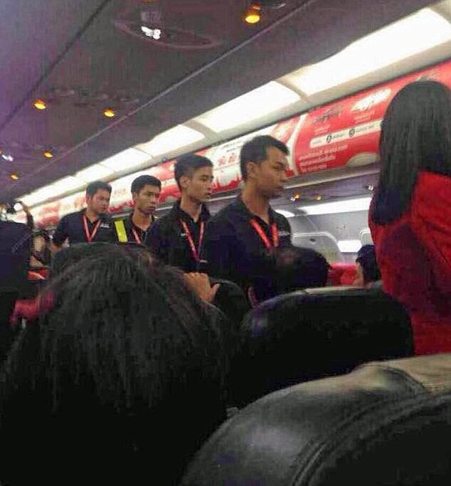 "Pic shows: A Chinese couple got into a furious row with cabin crew on a flight. A Chinese couple who got into a furious row with cabin crew on a flight could find themselves separated for quite some time after the incident escalated when hot noodles were thrown into the face of a hostess. The incident which happened on a Thai AirAsia plane was captured on video camera and on mobile phone snaps taken by other passengers that show one of the hostesses touching her face after being scalded when she was hit with a hot dish. She was reportedly given first aid on board by her colleagues to deal with the burns and was taken to hospital after the flight turned around and landed back in the Thai capital Bangkok. The trouble started when the couple boarded the plane and found themselves seated separately on the charter flight from Bangkok to the Chinese city of Nanjing. And even though the seating was rearranged to put the couple together, they were still angry and refused to calm down. The video clip showing the man shouting at staff who are trying to restrain him quickly went viral after it was uploaded on Chinese social media network Weibo. A spokesman for the budget airline said that the plane had been forced to turn round so that the angry couple could be arrested. The spokesman said that the decision to turn around had been made after the man claimed to have a bomb and threatened to blow the plane up. Photos later showed the man being led off the plane while carrying a young girl although he and the child and his girlfriend were not immediately arrested. He claimed that the hostess had been scalded by accident when they had argued with her over the receipt they wanted for the hot water. However after the incident went viral, officials from China's National Tourism Administration said the tourists had disrupted the flight, hurt other passengers and ""badly damaged the overall image of the Chinese people"". It comes at a time when the Chinese are travelling more but also becoming notorious for rough behaviour. More than 100 million people from China have travelled overseas this year, more than any other country. Incidents involving Chinese tourists making angry outbursts have prompted Beijing to issue stern guidelines on behaving abroad. In public service announcements even President Xi Jinping himself reminding citizens in China to improve their behaviour whilst travelling. (ends)"
